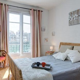 Exemple d'une chambre parentale chic de taille moyenne avec un mur blanc et un sol en bois clair.