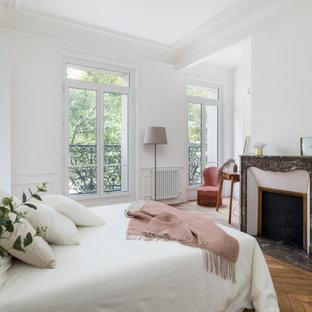 Idées déco pour une chambre parentale contemporaine avec un mur blanc, un sol en bois brun et une cheminée standard.