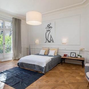 Réalisation d'une chambre design avec un mur blanc, un sol en bois brun, un sol marron et du lambris.