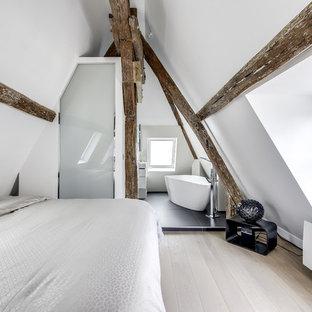 Cette photo montre une chambre adulte tendance avec un mur blanc, un sol en bois clair, aucune cheminée et un sol beige.