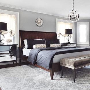 Cette image montre une grande chambre parentale traditionnelle avec un mur gris, aucune cheminée et un sol en bois foncé.