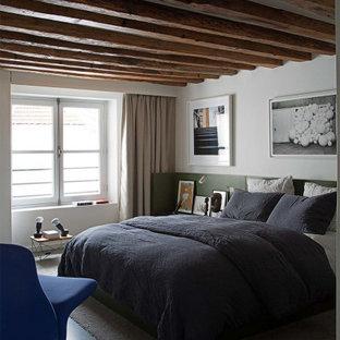 Cette photo montre une chambre tendance avec un mur blanc, béton au sol, un sol gris et un plafond en poutres apparentes.