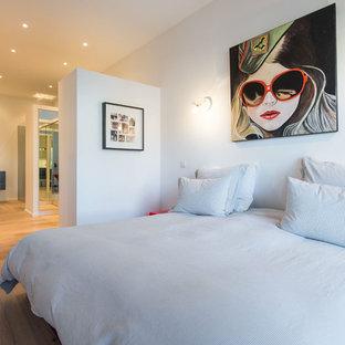Cette image montre une chambre design avec un mur blanc et un sol en bois brun.