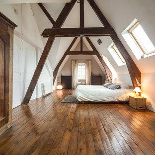 Inspiration pour une chambre rustique avec un mur blanc et un sol en bois brun.