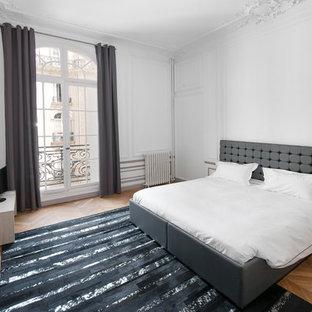 Exemple d'une grand chambre parentale tendance avec un mur blanc et un sol en bois brun.