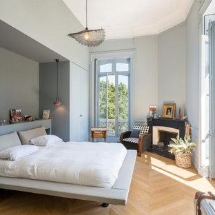 Modern inredning av ett stort huvudsovrum, med grå väggar, ljust trägolv, en öppen hörnspis, en spiselkrans i betong och beiget golv