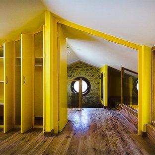 Idée de décoration pour une grande chambre mansardée ou avec mezzanine design avec un mur jaune.
