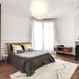 Aménagement d'une chambre classique avec un mur blanc, un sol en bois brun et une cheminée d'angle.