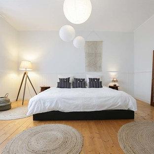 Ispirazione per una camera matrimoniale country di medie dimensioni con pareti bianche, parquet chiaro e pavimento giallo