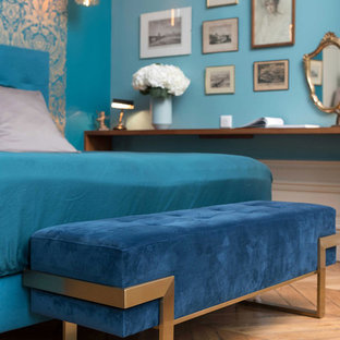 Example of a mid-sized ornate guest light wood floor and beige floor bedroom design in Lyon with blue walls