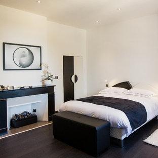 Aménagement d'une chambre parentale contemporaine de taille moyenne avec un mur blanc, une cheminée standard, un sol en bois foncé et un manteau de cheminée en bois.