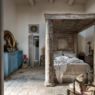 Cette image montre une grand chambre parentale rustique avec un mur blanc.