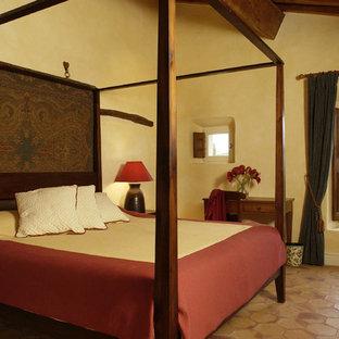 Ejemplo de habitación de invitados tradicional, de tamaño medio, con paredes amarillas y suelo de baldosas de terracota