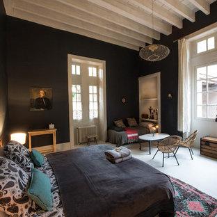 Cette image montre une grand chambre parentale bohème avec un mur noir et aucune cheminée.