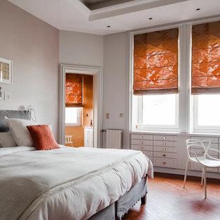 Cette photo montre une chambre tendance avec un mur gris, un sol en bois brun et un sol marron.