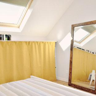 Modelo de dormitorio principal, moderno, grande, sin chimenea, con paredes púrpuras y suelo de madera clara