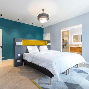 Exemple d'une chambre parentale tendance avec un mur bleu et un sol beige.
