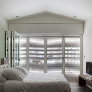 Cette image montre une chambre parentale minimaliste de taille moyenne avec un mur blanc.