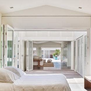 Cette photo montre une chambre parentale bord de mer de taille moyenne avec un mur blanc et un sol en bois clair.