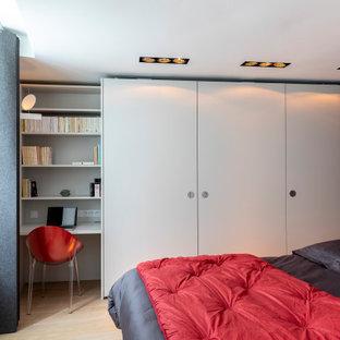 Idée de décoration pour une chambre parentale design de taille moyenne avec un mur blanc, un sol en bois clair et un sol beige.