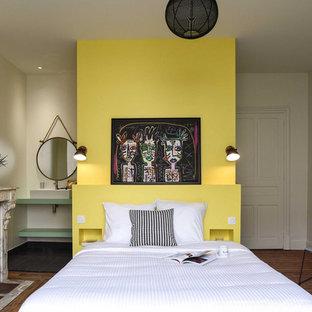 Modernes Hauptschlafzimmer mit gelber Wandfarbe, braunem Holzboden, Kamin und braunem Boden in Sonstige