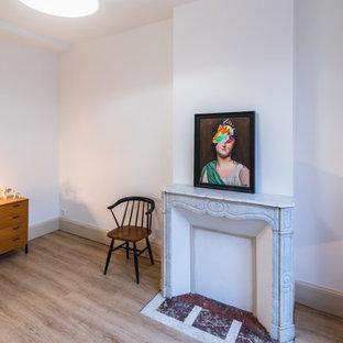 Diseño de dormitorio principal, retro, de tamaño medio, con paredes blancas, suelo de linóleo, chimenea tradicional, marco de chimenea de piedra y suelo marrón