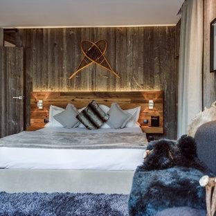 Modelo de dormitorio principal, rural, grande, sin chimenea, con suelo de madera en tonos medios