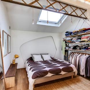 Cette photo montre une chambre éclectique avec un mur blanc et un sol en bois clair.