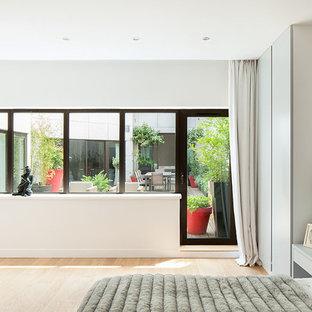 Idée de décoration pour une grande chambre parentale design avec un mur blanc et un sol en bois clair.