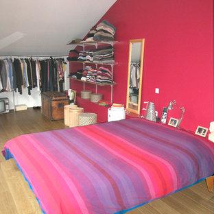 Imagen de dormitorio principal, industrial, con paredes rojas y suelo de madera clara