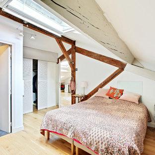 Inspiration pour une chambre parentale ethnique de taille moyenne avec un mur blanc, un sol en bois brun et un sol marron.