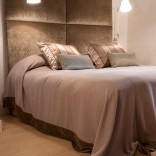 Cette image montre une chambre parentale design de taille moyenne avec un mur blanc et un sol en bois brun.