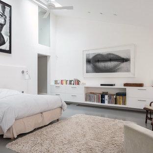 Exemple d'une grand chambre parentale tendance avec un mur blanc, béton au sol, un sol gris et aucune cheminée.