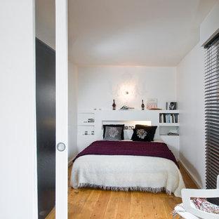 Idées déco pour une chambre contemporaine avec un mur blanc et un sol en bois brun.