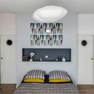 Inspiration pour une chambre parentale nordique de taille moyenne avec un mur gris et un sol en bois brun.