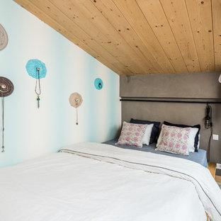 Cette photo montre une chambre mansardée ou avec mezzanine tendance de taille moyenne avec un mur gris, béton au sol et aucune cheminée.