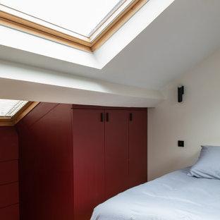 Diseño de dormitorio urbano, de tamaño medio, con paredes rojas y suelo de madera clara