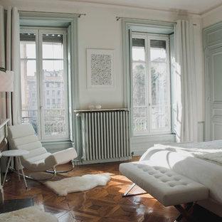 Inspiration pour une chambre traditionnelle avec un mur blanc et un sol en bois brun.