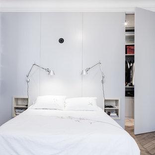 Cette image montre une chambre parentale design de taille moyenne avec un mur gris, un sol en bois brun, une cheminée standard et un manteau de cheminée en pierre.