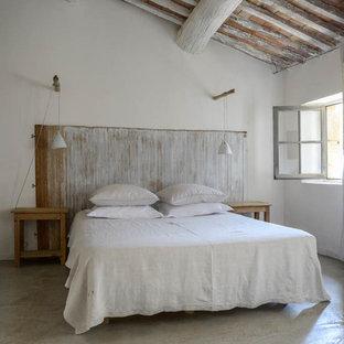 Idée de décoration pour une chambre d'amis champêtre de taille moyenne avec un mur blanc, béton au sol et aucune cheminée.