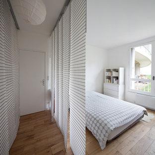 Réalisation d'une chambre parentale design de taille moyenne avec un mur blanc, un sol en bois clair, aucune cheminée et un sol beige.