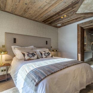 Exemple d'une grande chambre adulte montagne avec un mur beige, un sol en bois brun et un sol marron.