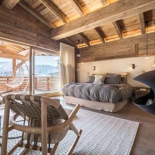 Großes Rustikales Hauptschlafzimmer mit beiger Wandfarbe, braunem Holzboden, Hängekamin und Kaminumrandung aus Metall in Lyon
