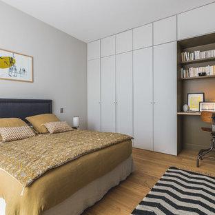Inspiration pour une chambre design avec un mur blanc, un sol en bois brun et un sol marron.