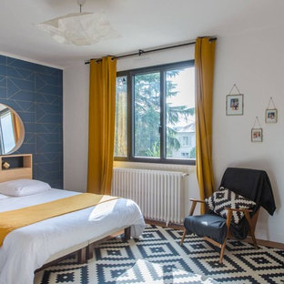 Cette image montre une grand chambre parentale design avec un mur bleu, un sol en bois brun et un sol marron.