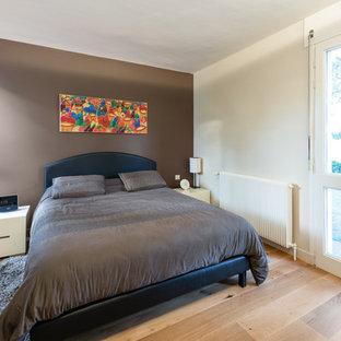 Modelo de dormitorio principal, actual, de tamaño medio, con paredes marrones, suelo de travertino y suelo beige