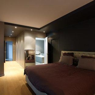 Foto de dormitorio principal, minimalista, de tamaño medio, con paredes grises, suelo laminado y suelo beige