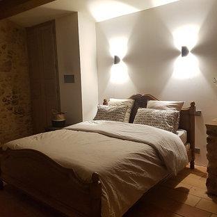 Diseño de dormitorio principal, de estilo de casa de campo, grande, con suelo de baldosas de terracota, chimeneas suspendidas y marco de chimenea de metal