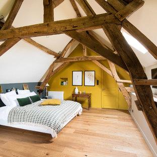Cette image montre une chambre rustique avec un mur jaune, un sol en bois clair et un sol beige.