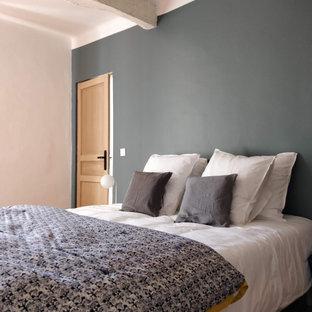 Cette photo montre une chambre d'amis méditerranéenne de taille moyenne avec un mur gris, un sol en carreau de terre cuite, aucune cheminée, un sol rouge et un plafond en poutres apparentes.